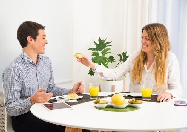 Mujer joven que alimenta el pan a su marido en el desayuno