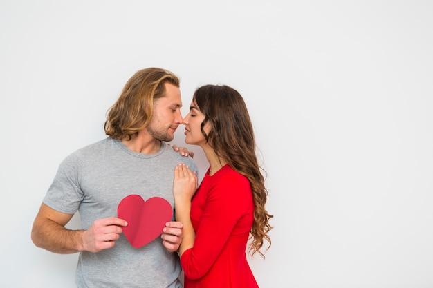 Mujer joven que ama a su novio que sostiene el papel de la forma del corazón disponible contra el contexto blanco