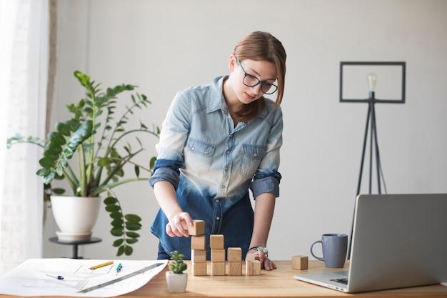Mujer joven que apila el bloque de madera en el escritorio del trabajo en la oficina