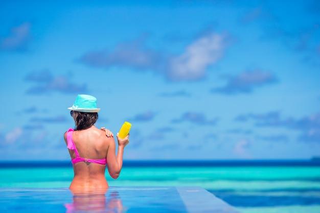Mujer joven que aplica la crema del sol durante vacaciones de la playa