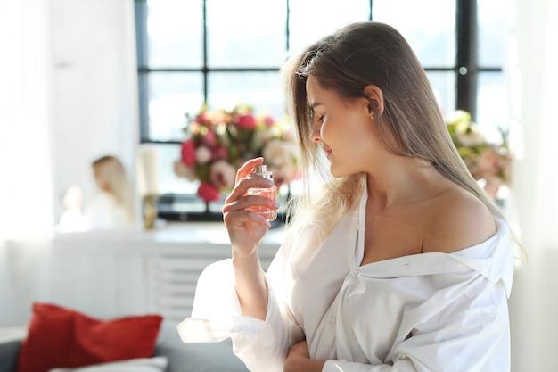 Mujer joven que aplica perfume.