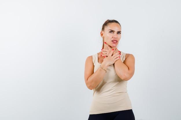 Mujer joven que se asfixia mientras saca la lengua en una camiseta sin mangas beige y se ve seria. vista frontal.