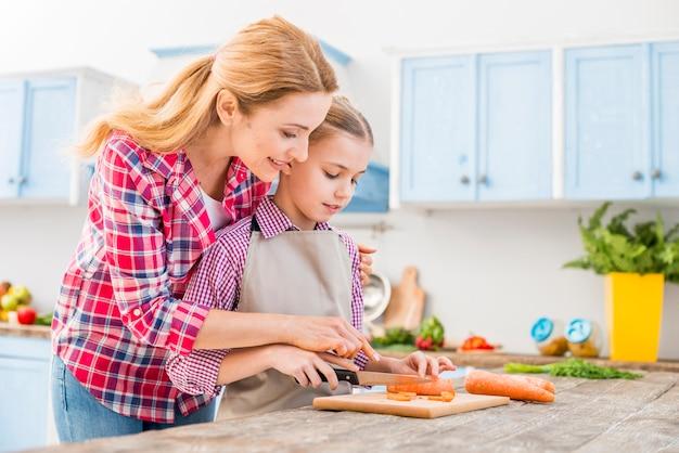 Mujer joven que ayuda a su hija que corta la zanahoria con el cuchillo en la tabla de madera