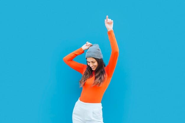 Mujer joven que baila con el brazo levantado delante de fondo azul