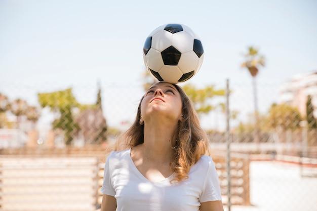 Mujer joven que balancea el balón de fútbol en la cabeza