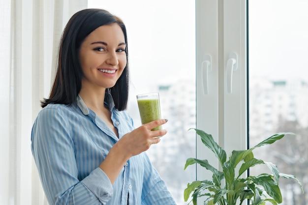 Mujer joven que bebe el batido verde recién mezclado de la fruta de kiwi