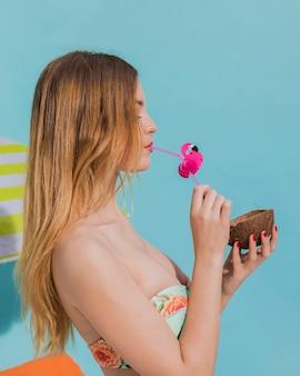 Mujer joven que bebe la bebida tropical en estudio
