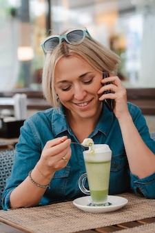 Mujer joven que bebe disfrutando del latte del té verde del matcha en mañana del verano en café.