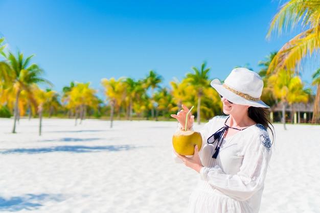 Mujer joven que bebe la leche de coco en día caluroso en la playa.