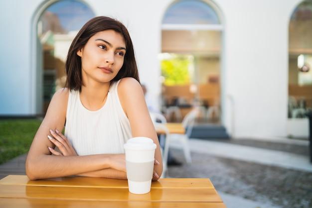 Mujer joven que bebe una taza de café en la cafetería.