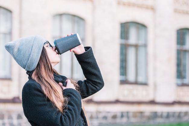 Mujer joven que bebe de la taza en la calle