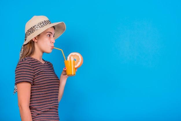 Mujer joven que bebe el zumo de naranja en fondo azul