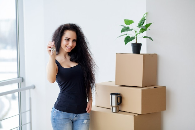 Mujer joven que cae la caja de cartón. mudarse a una nueva casa