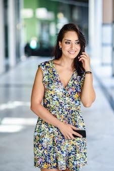 Mujer joven que camina en la calle que lleva el teléfono elegante.