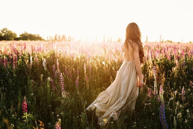 Mujer joven que camina en campo de flor en la puesta del sol en fondo.