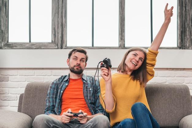 Mujer joven que celebra la victoria después de jugar el videojuego con su marido.