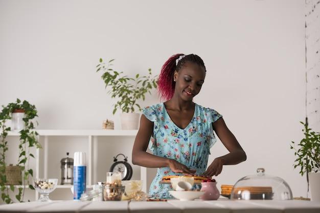 Mujer joven que cocina en casa