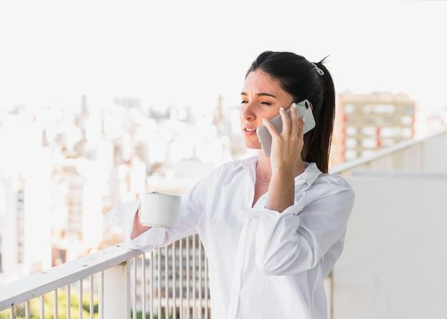 Mujer joven que se coloca en el balcón que sostiene la taza de café que habla en el teléfono móvil