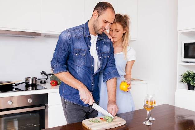 Mujer joven que se coloca cerca del marido que corta el bellpepper con el cuchillo en la tabla en la cocina