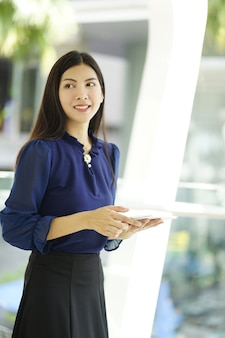Mujer joven que coloca y que sostiene la tableta que se coloca delante del edificio del negocio. al aire libre