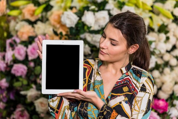 Mujer joven que se coloca con la tableta en casa verde