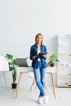 Mujer joven que se coloca con la tableta en gabinete