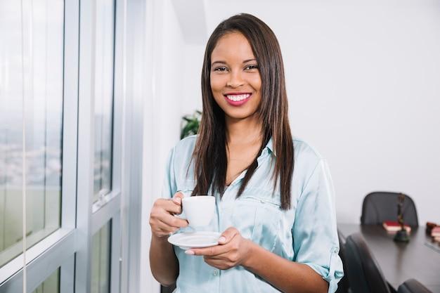 Mujer joven que se coloca con la taza de café en oficina