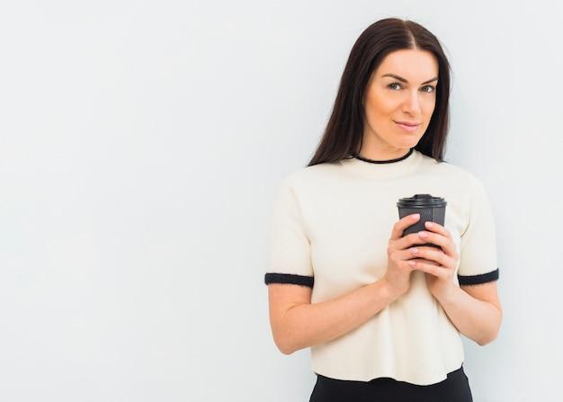 Mujer joven que se coloca con la taza de café