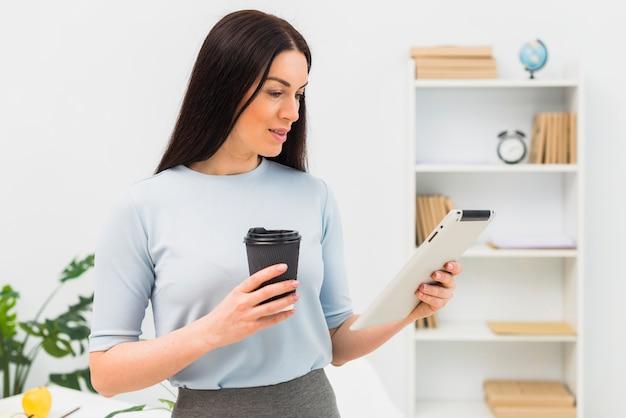 Mujer joven que se coloca con la taza y la tableta de café en oficina