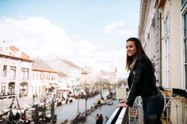 Mujer joven que se coloca en una terraza sobre la calle de la ciudad.