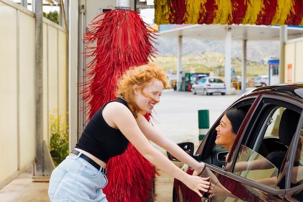 Mujer joven que se coloca en el túnel de lavado y que sonríe a la hembra asiática que mira fuera de la ventana de coche