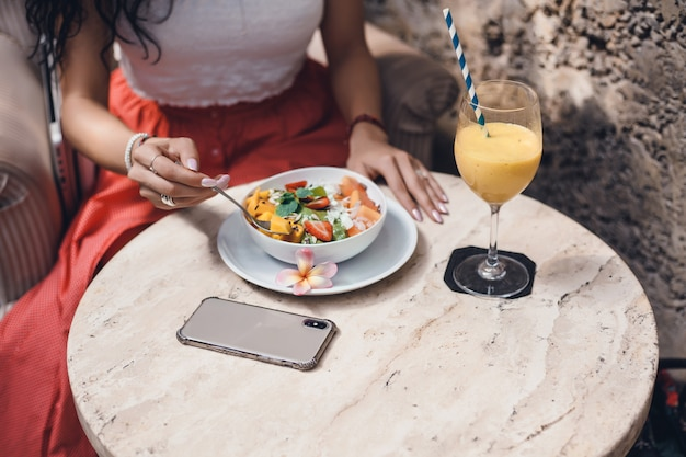 Mujer joven que come el batido en la cafetería, retrato feliz al aire libre