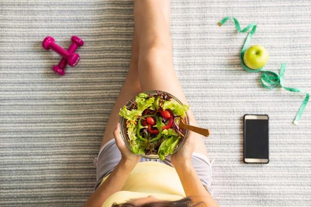 Mujer joven que come ensalada saludable hecha en casa en casa, estilo de vida saludable, concepto de dieta