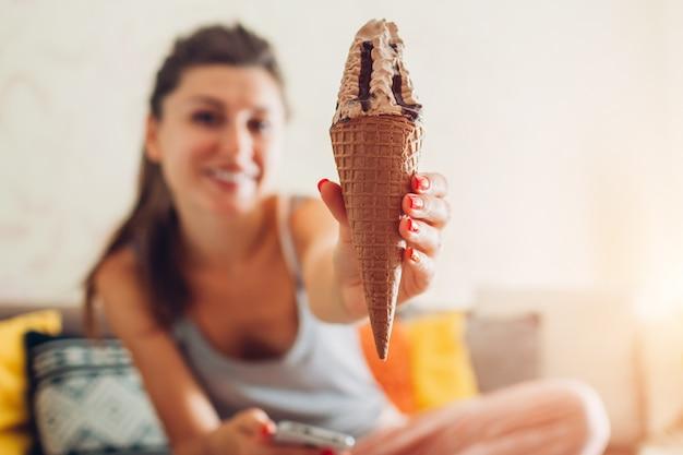 Mujer joven que come el helado de chocolate en el cono que se sienta en el sofá en casa.