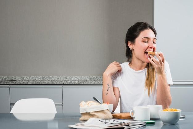 Mujer joven que come el pan en el desayuno