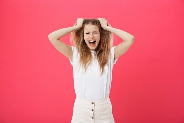 Mujer joven que consigue enojada, loca y gritando aislada en un fondo rosado.