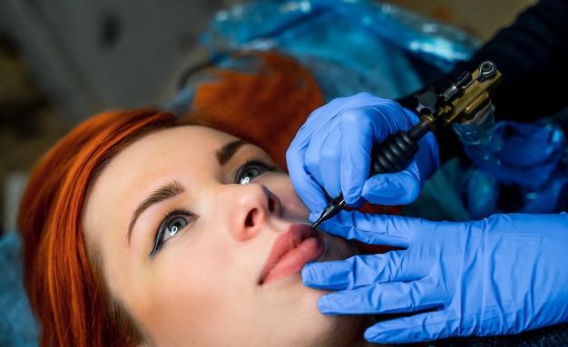 Mujer joven que consigue maquillaje permanente en los labios en el salón de belleza, primer plano