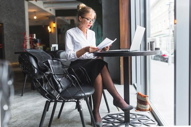 Mujer joven que controla el documento en el restaurante