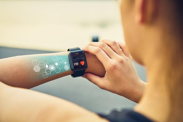 Mujer joven que controla el reloj de los deportes con el icono de la salud de la pantalla.
