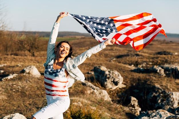 Mujer joven que corre con banderas americanas que agitan