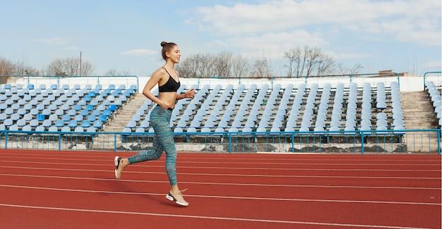 Mujer joven que corre durante mañana soleada en pista del estadio