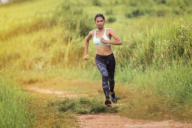 Mujer joven que corre en el rastro del bosque. saludable joven calentando al aire libre.