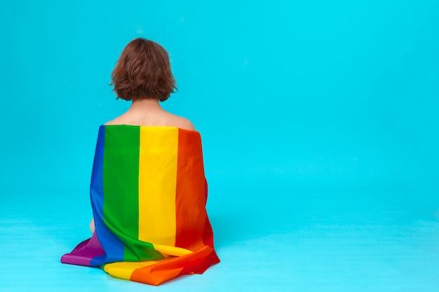 Mujer joven que cubre con la bandera del orgullo lgbt