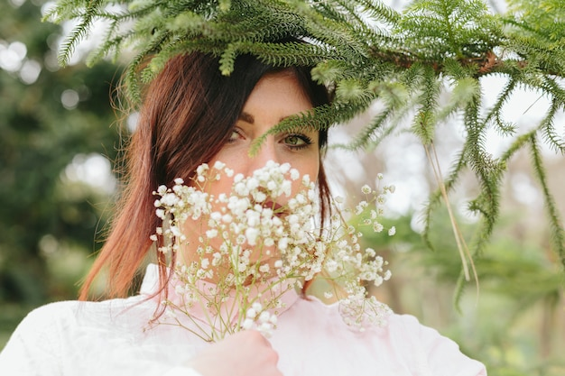 Mujer joven que cubre la cara con flores