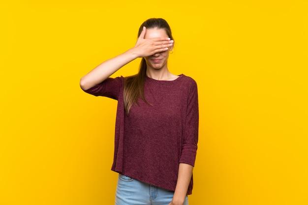 Mujer joven que cubre ojos por las manos. no quiero ver algo