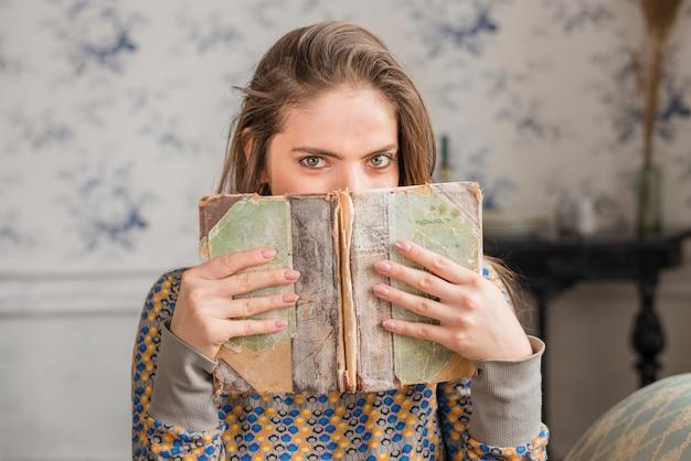 Mujer joven que cubre su boca con el libro desgastado desgastado