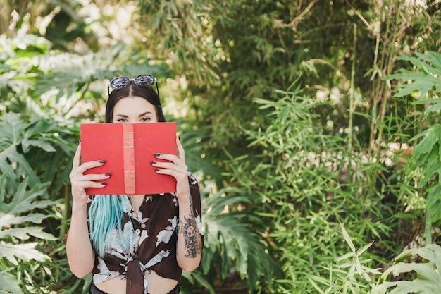 Mujer joven que cubre su boca con el libro que se coloca delante de las plantas crecientes