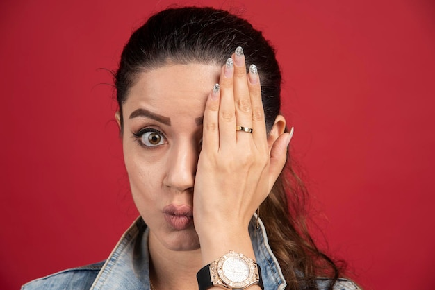 Mujer joven que cubre su ojo con la mano sobre un fondo rojo. foto de alta calidad