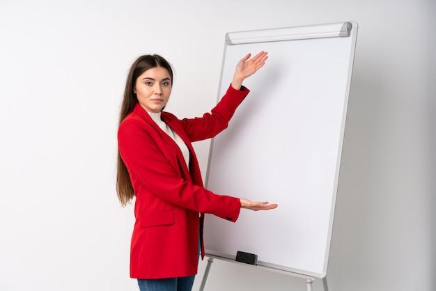 Mujer joven que da una presentación en el tablero blanco que da una presentación en el tablero blanco