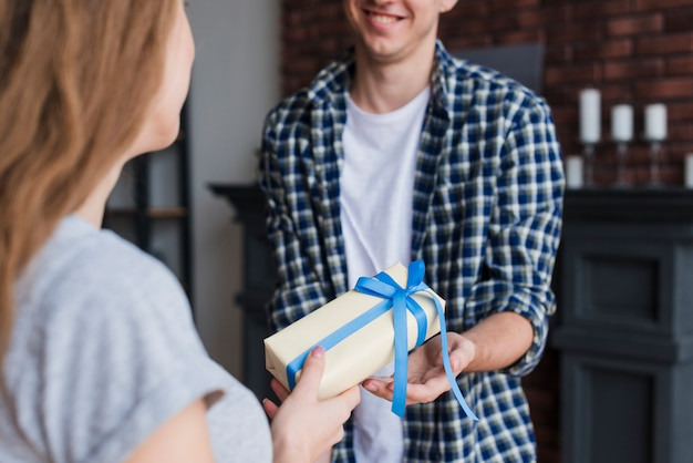 Mujer joven que da el regalo al marido